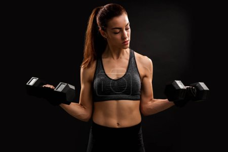 Photo for Fit female athlete lifting dumbbells against black background - Royalty Free Image