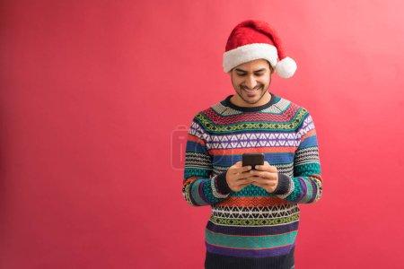 Photo pour Messagerie textuelle latine heureuse d'homme sur le smartphone tout en célébrant Noel contre le fond simple - image libre de droit