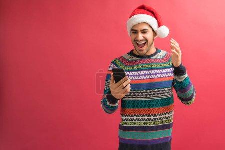 Photo pour Homme étonné avec la bouche ouverte regardant le smartphone tout en lisant le message texte sur le fond rouge - image libre de droit