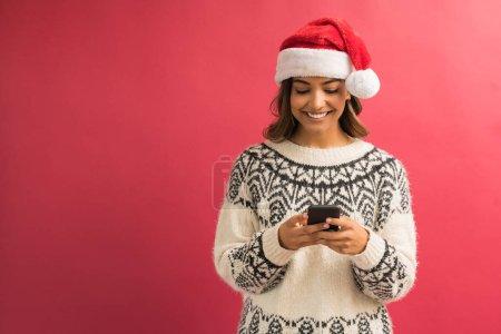 Photo pour Messagerie textuelle latine heureuse de femme sur le smartphone tout en célébrant Noel contre le fond simple - image libre de droit