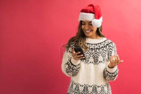 Photo pour Jeune belle femme souriant tout en lisant le message texte sur le smartphone sur le fond rouge - image libre de droit