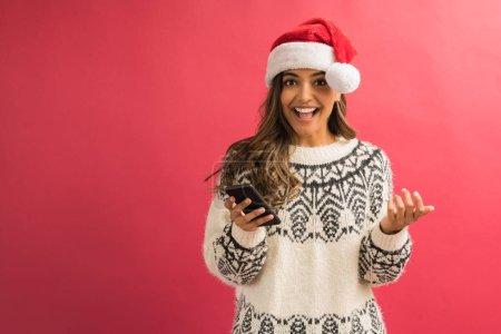 Photo pour Femelle attirante étonnée avec la main ouverte de bouche au smartphone tout en restant dans le studio - image libre de droit