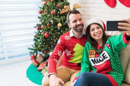 Photo pour Femme heureux prenant le selfie avec l'amant sur le smartphone à la maison pendant Noel - image libre de droit