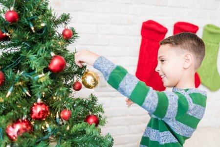 Photo pour Vue latérale du garçon souriant décorant l'arbre de Noël à la maison - image libre de droit