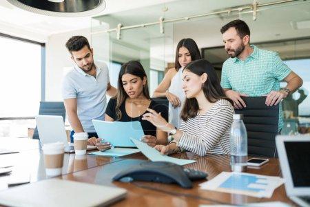 Photo pour Équipe de professionnels des affaires discutant de dossiers au bureau de création pendant la réunion - image libre de droit
