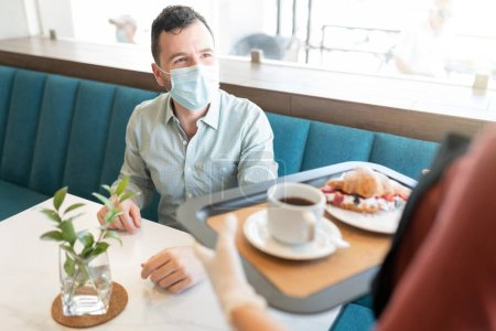 Photo for Caucasian man in face mask looking at waitress serving in coffee shop - Royalty Free Image