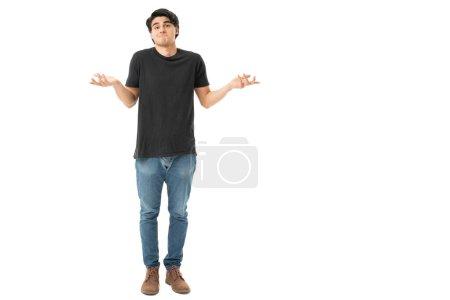 Foto de Longitud completa de la expresión del hombre joven despistado de pie sobre fondo blanco - Imagen libre de derechos