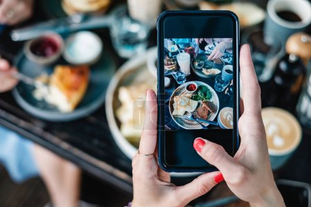 person taking photo  of food with smartphone