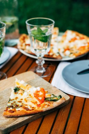Photo for Delicious pizza on dinner table in garden - Royalty Free Image