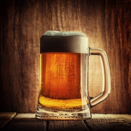 Mug of beer with foam on wooden background
