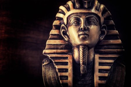 Stone pharaoh Tutankhamen mask on dark background...