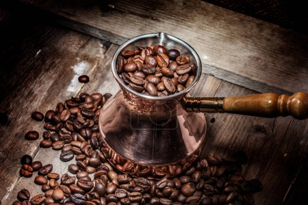 Photo for Scattered coffee beans and copper coffee turk on wooden background - Royalty Free Image