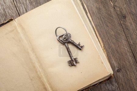 Photo pour Deux anciennes clés rouillées sur livre antique - image libre de droit