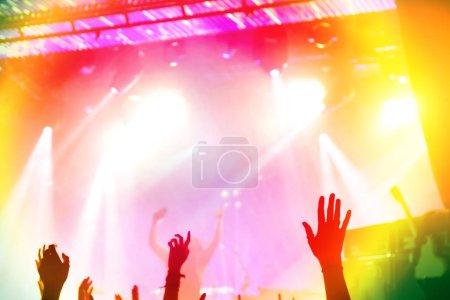 Photo pour Silhouettes de fans et de musiciens sur scène, projecteurs lumineux au concert de musique - image libre de droit