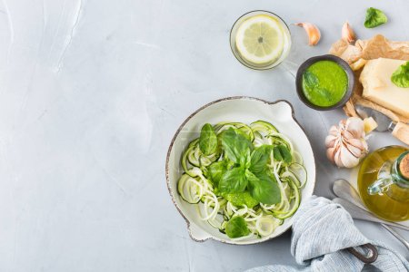 Photo for Food and drink, healthy eating and dieting concept. Seasonal fresh raw zucchini spaghetti pasta noodles with spinach pesto sauce and ingredients on the kitchen table. Top view flat lay background - Royalty Free Image