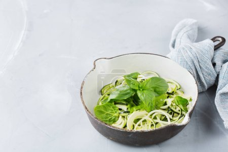 Photo for Food and drink, healthy eating and dieting concept. Seasonal fresh raw zucchini spaghetti pasta noodles with spinach pesto sauce on the kitchen table - Royalty Free Image