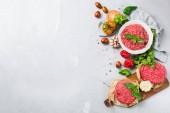 """Постер, картина, фотообои """"Здоровое питание, приготовление концепции. Домашнее сырые органические фарша мясо и гамбургер котлеты стейк с овощами на белом столе. Скопировать космический фон, кладут плоский вид сверху"""""""