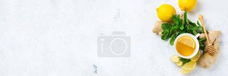 Photo pour Nourriture et boissons, concept de soins de santé nature morte. Boisson au thé au gingembre dans une tasse blanche avec du miel de menthe citron sur une table de cuisine pour les journées d'automne d'hiver froides et grippales. Vue supérieure copier l'espace arrière-plan - image libre de droit