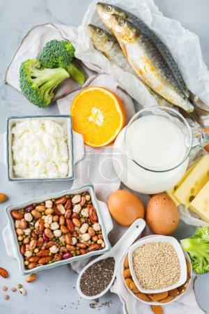 Photo pour Nutrition équilibrée, concept de restauration saine. Assortiment de sources de nourriture riches en calcium, haricots, produits laitiers, sardines, brocoli, graines de clerbois, amandes sur une table de la cuisine - image libre de droit