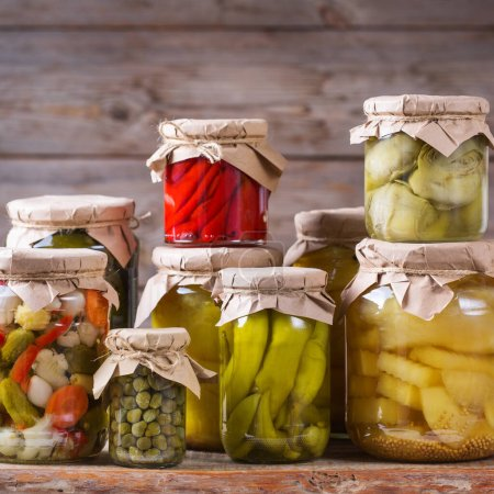 Photo for Preserved and fermented food. Assortment of homemade jars with variety of pickled and marinated vegetables on a wooden table. Housekeeping, home economics, harvest preservation - Royalty Free Image