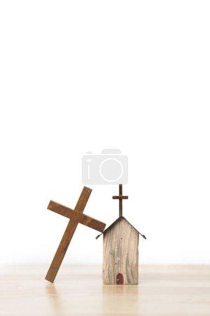 Photo pour Croix en bois appuyée sur une petite maison modèle en bois sur planche en bois et fond blanc - image libre de droit