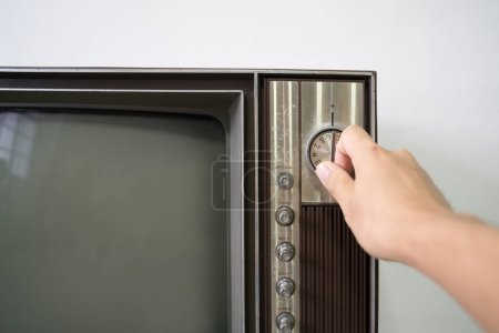 Photo for Hand switching on analog old retro television - Royalty Free Image