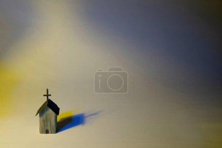 Photo pour Eglise en bois coloré avec un éclairage sévère sur fond pastel. Conceptuel sur l'acceptation de toutes les couleurs - image libre de droit