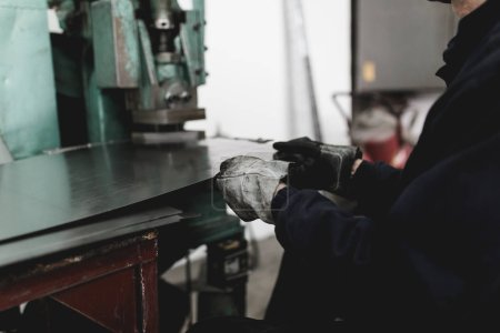 Metallurgy industry. Factory for production of heavy pellet stoves and boilers. Manual worker preparing parts for production. Selective focus.