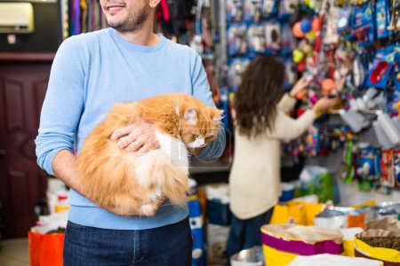 Man holding his persian cat in pet shop. Selective focus on cat.