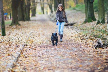 Photo pour Chiot bouledogue français en promenade avec son enfant propriétaire le jour d'automne dans le parc. L'accent est mis sur chien . - image libre de droit