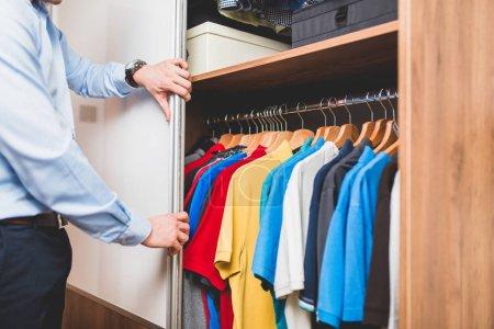 Young man choosing t-shirt from wardrobe.