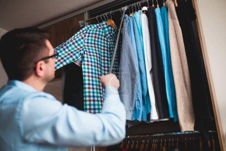 Young man choosing shirt from wardrobe.