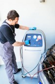 Man checking Freon level in air conditioner compressor.