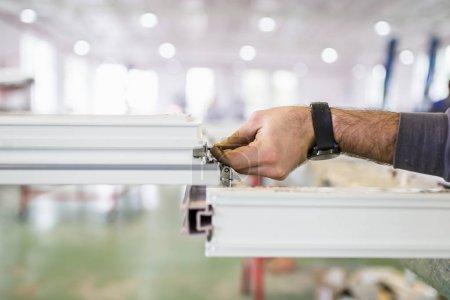 Photo pour Usine pour la production de portes et fenêtres en aluminium, bois et PVC. Ouvrier assemblant portes et fenêtres en PVC. Concentration sélective . - image libre de droit