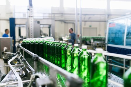 Photo for Water factory - Water bottling line for processing and bottling pure mineral water into green glass bottles. Selective focus. - Royalty Free Image