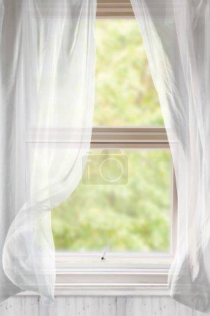 Photo pour Fenêtre ouverte avec rideaux de voile soufflant dans la brise - image libre de droit