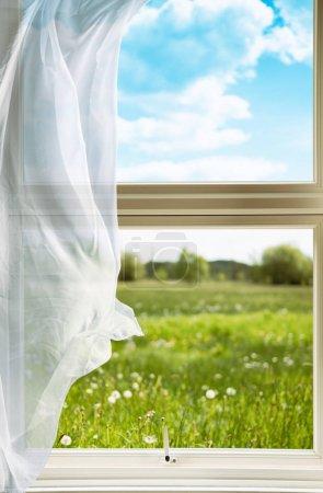 Photo pour Fenêtre ouverte avec rideaux de voile soufflant dans la brise donnant sur la campagne - image libre de droit