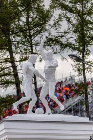 Russia, Yekaterinburg - June 15, 2018: Sculptures of football players against background of filled stands of Egypt - Uruguay match of central stadium of Ekaterinburg. World Cup 2018 in Russia