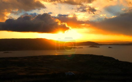 A beautiful colourful sunset over Lake Titicaca from Taquile Island in Peru, but looking across to Bolivia.