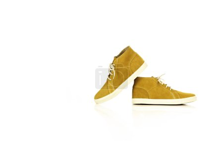 Photo for A pair of elegant suede nubuck leather casual yellowish sporty shoes one on top of other isolated on white background. Studio shot. Copy space. - Royalty Free Image