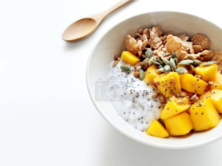 Photo for Healthy breakfast bowl with chia seeds pudding, mango, cereal, pumpkin seeds and sunflower seeds on a kitchen table with copy space - Royalty Free Image