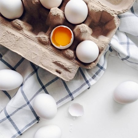 Organic white eggs in package on a kitchen table, egg yolk top view