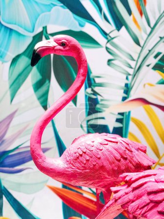 Pink flamingo statue decorated with colorful tropical summer graphic background