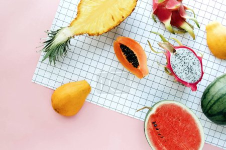 Flat lay tropical summer fruit on a white grid and pastel pink background. Creative food concept with pineapple, watermelon, Hawaii papaya, dragon fruit