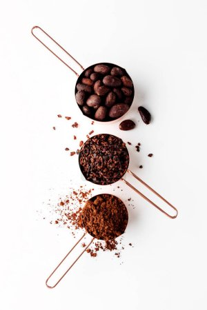 Rose gold measuring cups of cocoa beans, cacao nip...
