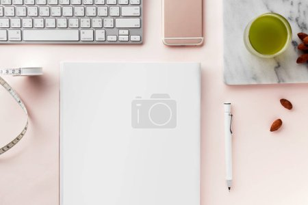 Photo for Creative flat lay workspace with minimal style. Modern desk with computer, smartphone, magazine, notebook, pencil, tapeline, almonds and a glass of green tea on a pastel pink background, top view - Royalty Free Image