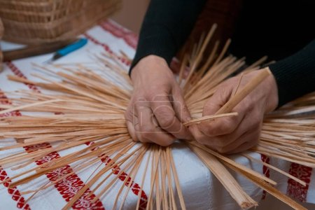 skilled woman plaits a straw bag at ethnographic master class, traditional craft art