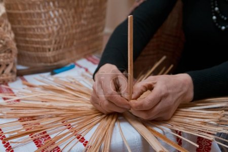 Vinnytsia, Ukraine - 19.03.2018: skilled woman plaits a straw bag at ethnographic master class, traditional craft art at ethnographic master class