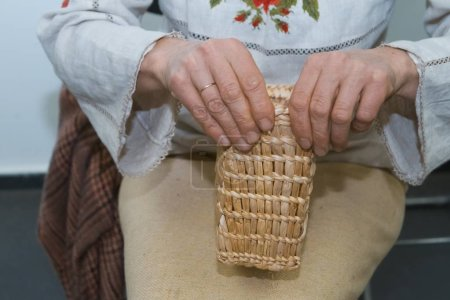 skilled woman artist plaits a straw bag, traditional craft art, ecological material, fabric