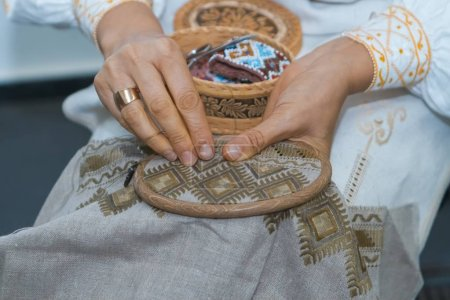 Craft embroidery, woman's hands decorate handmade linen canvas with color thread, embroider traditional Ukraininan ornament, folklore art